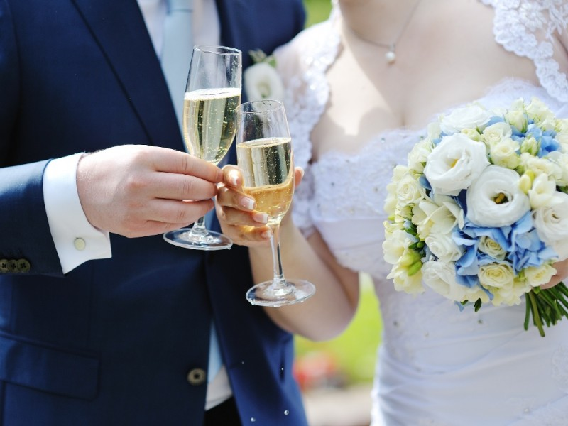 Bride and groom making a toast with champagne glasses after wedding ceremony